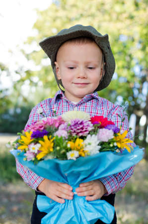 Smiling little boy presenting a bunch of flowers to his Mum on Mothers day or his Valentine sweetheart Stock Photo - 15277422
