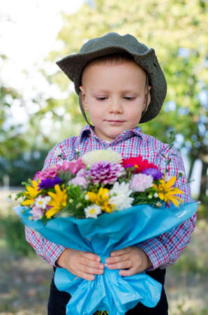 Cute little boy with a serious expression holding a large colourful bunch of flowers for his Valentine or mother Stock Photo - 15277425