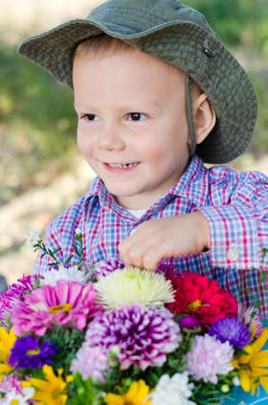 Mischievous little boy with a lovely grin holding a large bouquet of assorted colourful flowers outdoors Stock Photo - 15277428