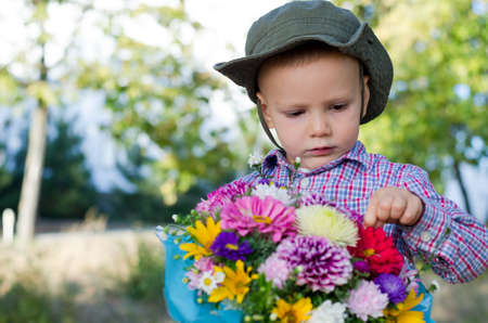 Cute little boy with a large bunch of flowers in giftwrap inspecting the petals of a flower with copyspace Stock Photo - 15277430