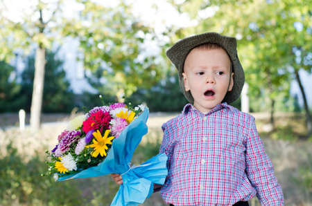 Self-conscious little boy singing with a large bouquet of flowers in his hand for his mother on Valentines or Mothers Day Stock Photo - 15277447