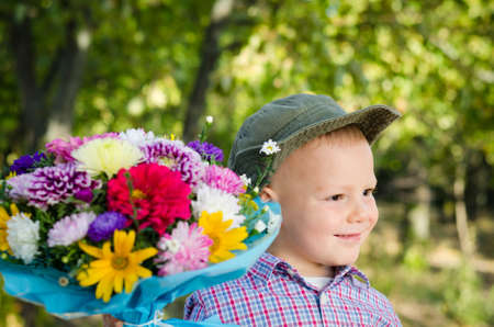 Smiling little boy in a hat with a large bouquet flowers for a loved one on Valentines or Mothers Day Stock Photo - 15277434
