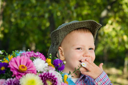 Cute smiling boy with bouquet of flowers Stock Photo - 15277432