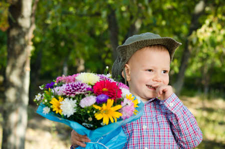 bashful: Bashful small boy smiling sheepishly with a bouquet of flowers for his sweetheart or Mum on Valentines or Mothers day Stock Photo