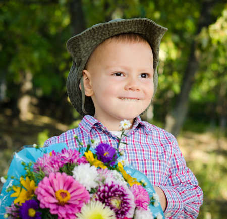 Little boy with a large bunch of colourful flowers for his sweetheart on Valentines day Stock Photo - 15277421