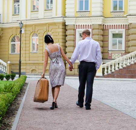 Paar wandelen weg van de camera hand in hand met de vrouw leunend zijwaarts door het gewicht van de bagage die ze draagt Stockfoto