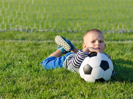 Cute young boy with a frown on his face lying on grass with a soccer ball as he waits for someone to play with him photo