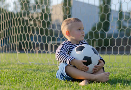 Little boy sitting in the goalposts with a soccer ball on his lap looking expectantly to the side as he waits for someone to play with photo