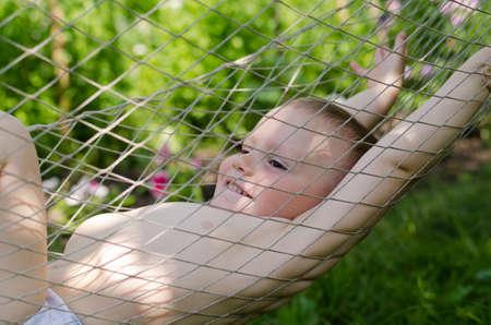 niño sin camisa: Lindo chico sin camisa poco de relax en una hamaca con una amplia sonrisa de placer en su rostro