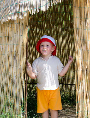 Excited little boy in colourful yellow shorts and sunhat standing in the entrance to a reed hut while exploring on vacation Stock Photo - 15872042