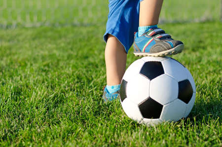 kids football: Little boy in shorts and trainers with his foot resting on top of a soccer ball on green grass with copyspace