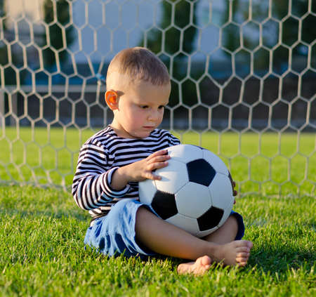 Little boy sitting barfoot on the green grass in the goal with his soccer ball on his lap lost in thought photo