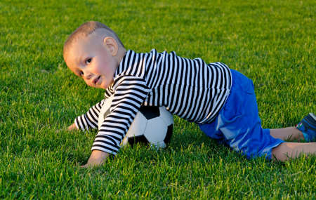 diving save: Cute little boy diving on a soccer ball to make a save while playing outdoors on a sportsfield in evening light