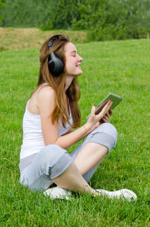 Young girl with a blissful expression sitting crosslegged on the green grass wearing headphones enjoying her music from the tunes on her tablet photo