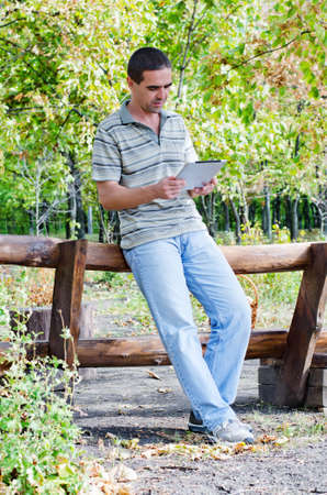 Attractive middle-aged man in jeans leaning on a timber fence in woodland with a tablet in his hands reading the information on the screen photo