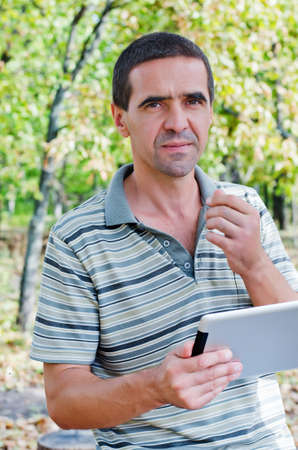 unemotional: Serious attractive middle-aged man standing outdoors amongst trees using a tablet