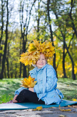 Little girl with colourful autumn headdress of bright yellow leaves that she has collected in the park photo