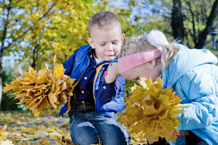 he   my sister: Little boy fascinated by an insect crawling on his hand as he and his sister kneel on the ground collecting colourful yellow autumn leaves