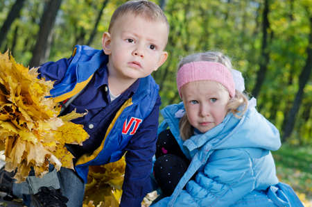 Portrait of young boy and girl gathering fallen autumn leaves photo