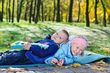 Little boy lying on his sister who is laughing while trying to wriggle out from under him on a mat in the park photo