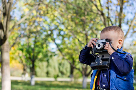 treed: Young boy taking a photograph with a vintage film slr camera in a treed garden with copyspace