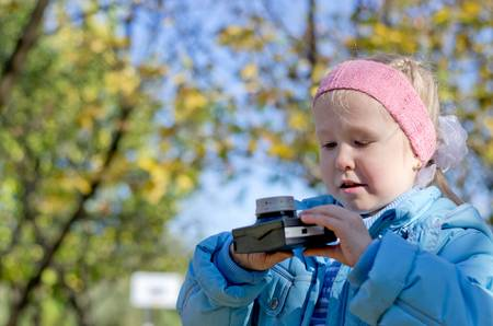 intrigued: Small girl intrigued by an old camera studying it intently as she stands outdoors in the park