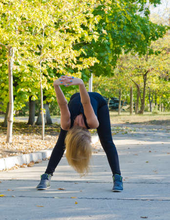 limbering: Supple woman bending over stretching her arms with her hands clasped together as she exercises in the park