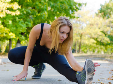 limbering: Woman athlete warming up in a park stretching her muscles before starting her training Stock Photo