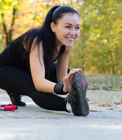 limbering: Happy woman exercising in a park bending forwards low on the ground touching her toes as she stretches her muscles