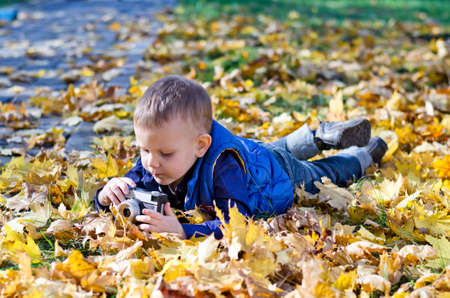 Cute small boy lying on the ground amongst fallen autumn leaves playing with a retro slr camera photo