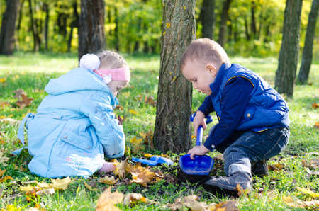Small young brother ans sister digging with a trowel at the base of a tree outdoors in a wooded park Stock Photo - 16140250