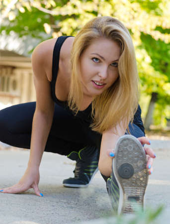 supple: Athletic supple wman exercising bending down low on the ground with her foot extended stretching her muscles as she touches her toes Stock Photo