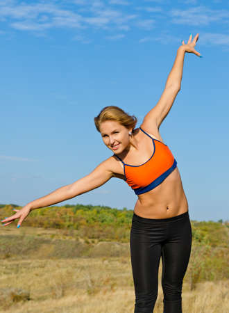 outspread: Beautiful healthy active young blonde woman with arms outspread in natural outdoor setting