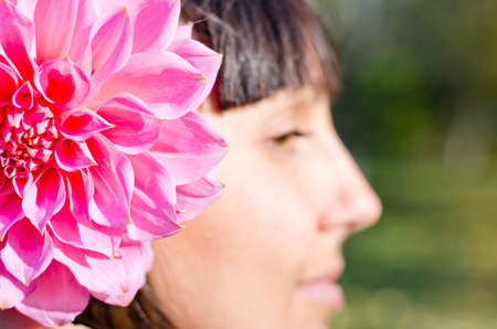 Woman with a beautiful large fresh pink dahlia in her hair with shallow dof and focus to the flower photo