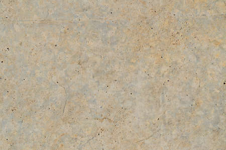 Abstract background texture of a clean concrete surface with small random pitted holes