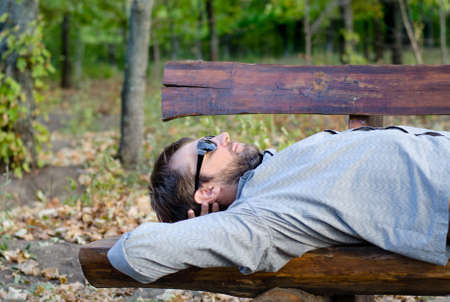 timber bench seat: Man sleeping on a rustic wooden bench lying back on the seat in the sunshine with his sunglasses on