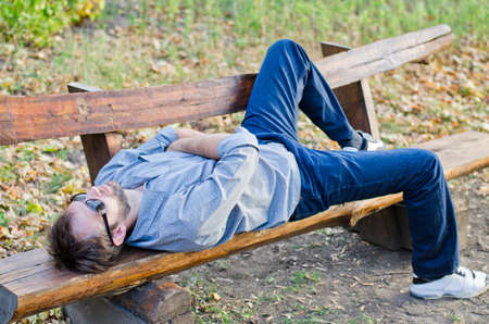 timber bench seat: Man with sunglasses relaxing in park on wooden bench