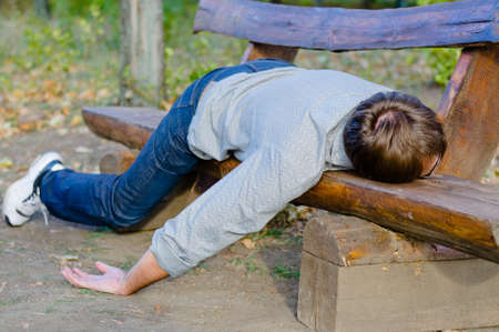 Passed out: Drunk man sleeping in park on wooden bench Stock Photo