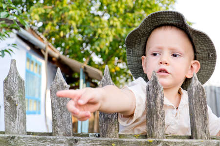 Cute little boy in a sunhat peering over the top of an old wooden picket fence and pointing through the slats with his hand Stock Photo - 16574148