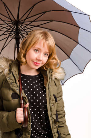 Attractive cheerful young blonde woman with a sweet smile sheltering under a large umbrella in a warm jacket looking at the camera isolated on white photo