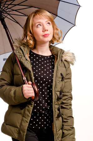 Hopeful young blonde woman checking out the weather as she stands under her umbrella looking up at the sky with a look of anticipation isolated on white photo