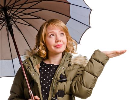 Smiling attractive young blonde woman standing under an umbrella holding out her hand to check for rain isolated on white photo