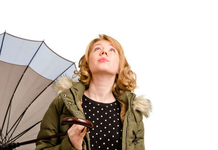 rueful: Attractive blonde woman holding an umbrella standing with her head tilted right back looking at the sky as she contemplates the weather isolated on white Stock Photo