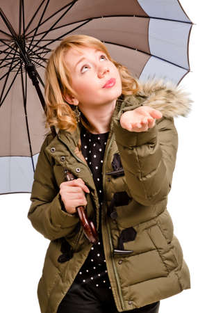 Young woman with umbrella checking if it rains - isolated on white photo