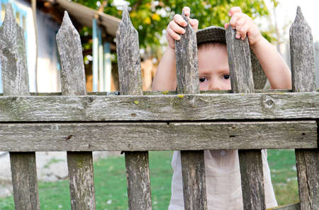 Little boy looking through a wooden picket fence Stock Photo - 16638068