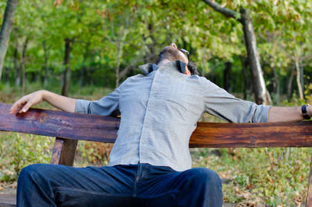 convalesce: Exhausted man relaxing on a bench in woodland with his head thrown back and his arms outspread along the top of the bench