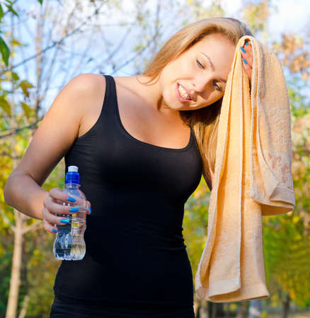 perspiring: Perspiring woman athlete wiping her brow with a towel as she stops for a breather to take a drink of water
