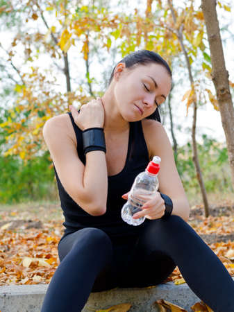 Woman athlete sitting on a curb in a park stretching her neck muscles and massaging them with her hand as she pauses for a drink of water photo
