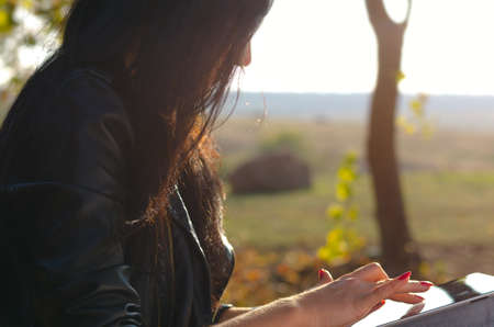 Closeup cropped side view of a woman using a tablet touching the screen with her finger against a background of open countryside Stock Photo