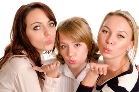 Three young beautiful mischievous ladies blowing kisses across their hands as they stand close together in a row isolated on white Stock Photo - 16795833